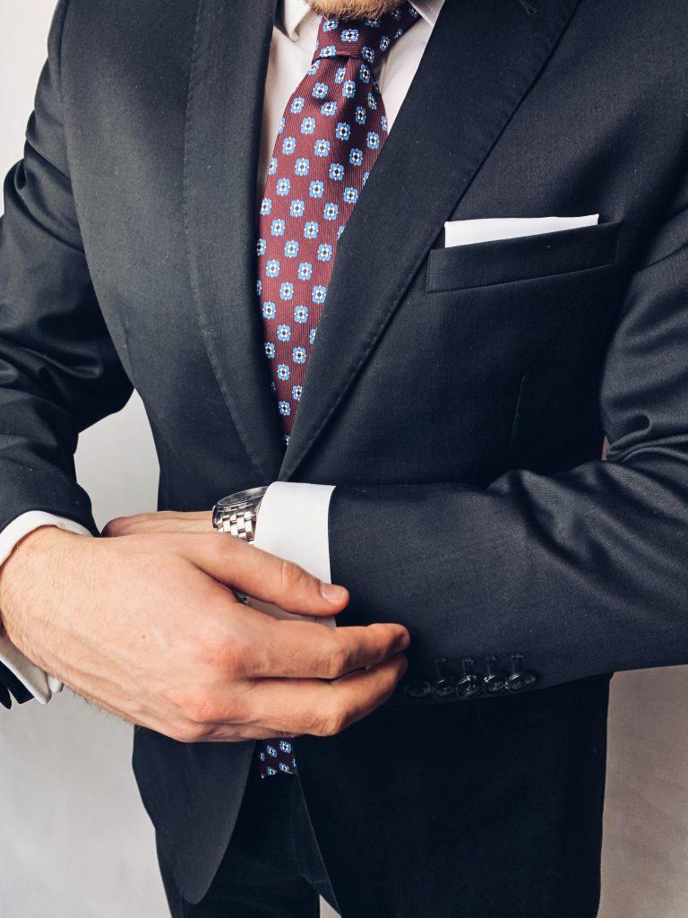 Czarny garnitur z dodatkami: bordowy jedwabny krawat oraz biała poszetka. Jak ubrać się na wesele?