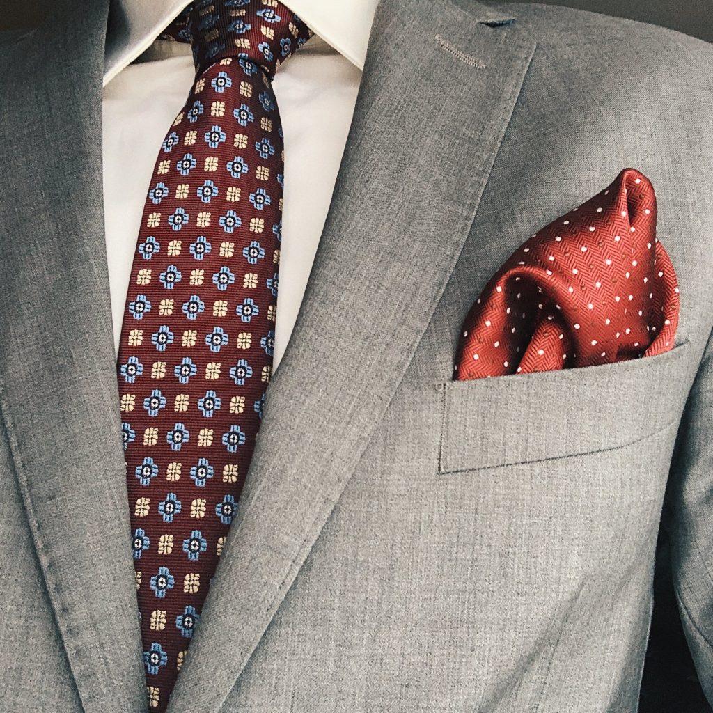 Szary garnitur z dodatkami: bordowy krawat oraz bordowa poszetka. Jak ubrać się na wesele?