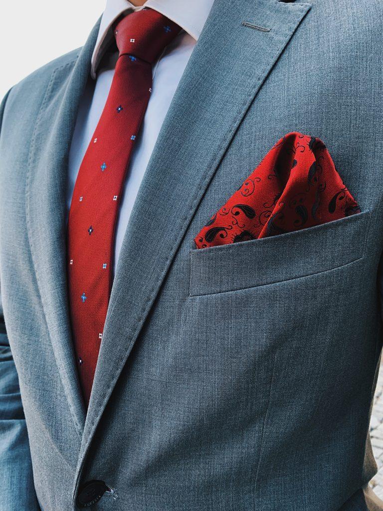 Szary garnitur z dodatkami: czerwony krawat oraz czerwona poszetka. Jak ubrać się na wesele?