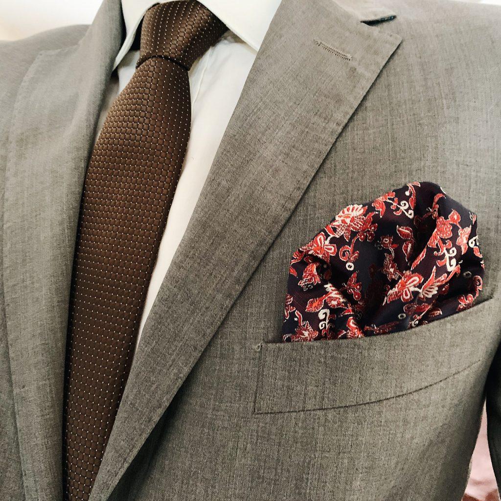 Szary garnitur z dodatkami: brązowy krawat oraz kwiecista poszetka. Jak ubrać się na wesele?