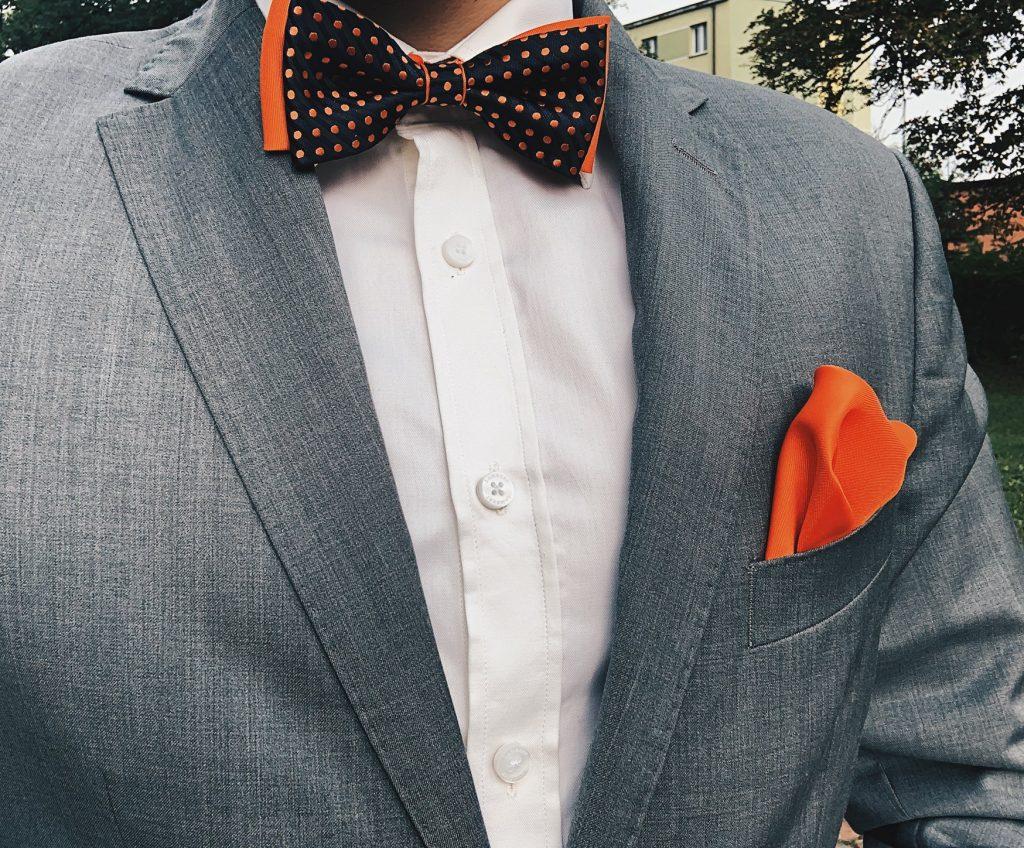 Szary garnitur z dodatkami: pomarańczowa muszka oraz pomarańczowa poszetka. Jak ubrać się na wesele?
